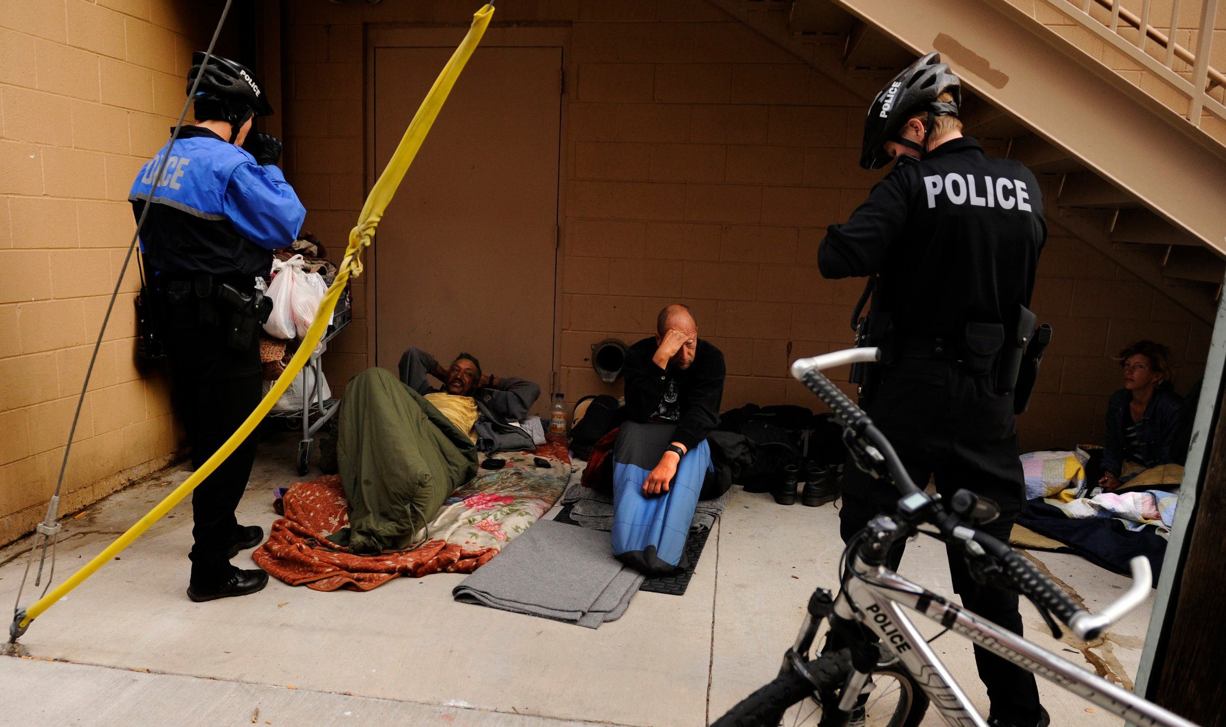 Denver Police Officers Layla DeStaffany, left, and Stephanie Meadows talk to a group of homeless sleeping, Wednesday, April 25, 2012, in an alley behind Central Baptist Church in Denver. The two officers, that are part of Denver Police Department's Homeless Outreach unit, asked them to move from the area. RJ Sangosti, The Denver Post  (Photo By RJ Sangosti/The Denver Post via Getty Images)