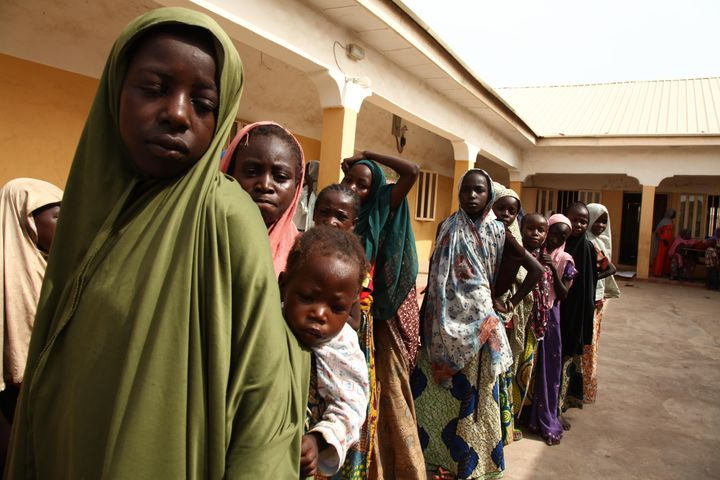 Girls rescued by Nigerian soldiers from Boko Haram line up to collect donated clothes at the Malkohi refugee camp.