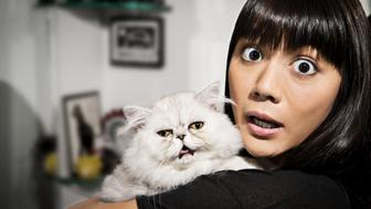 Surprised woman holding cat