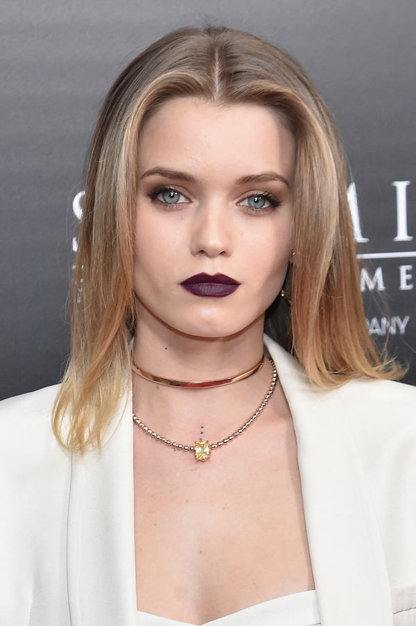The model/actress/musician is the picture of modern goth glam with her all-white ensemble and matte dark purple lipstick. The