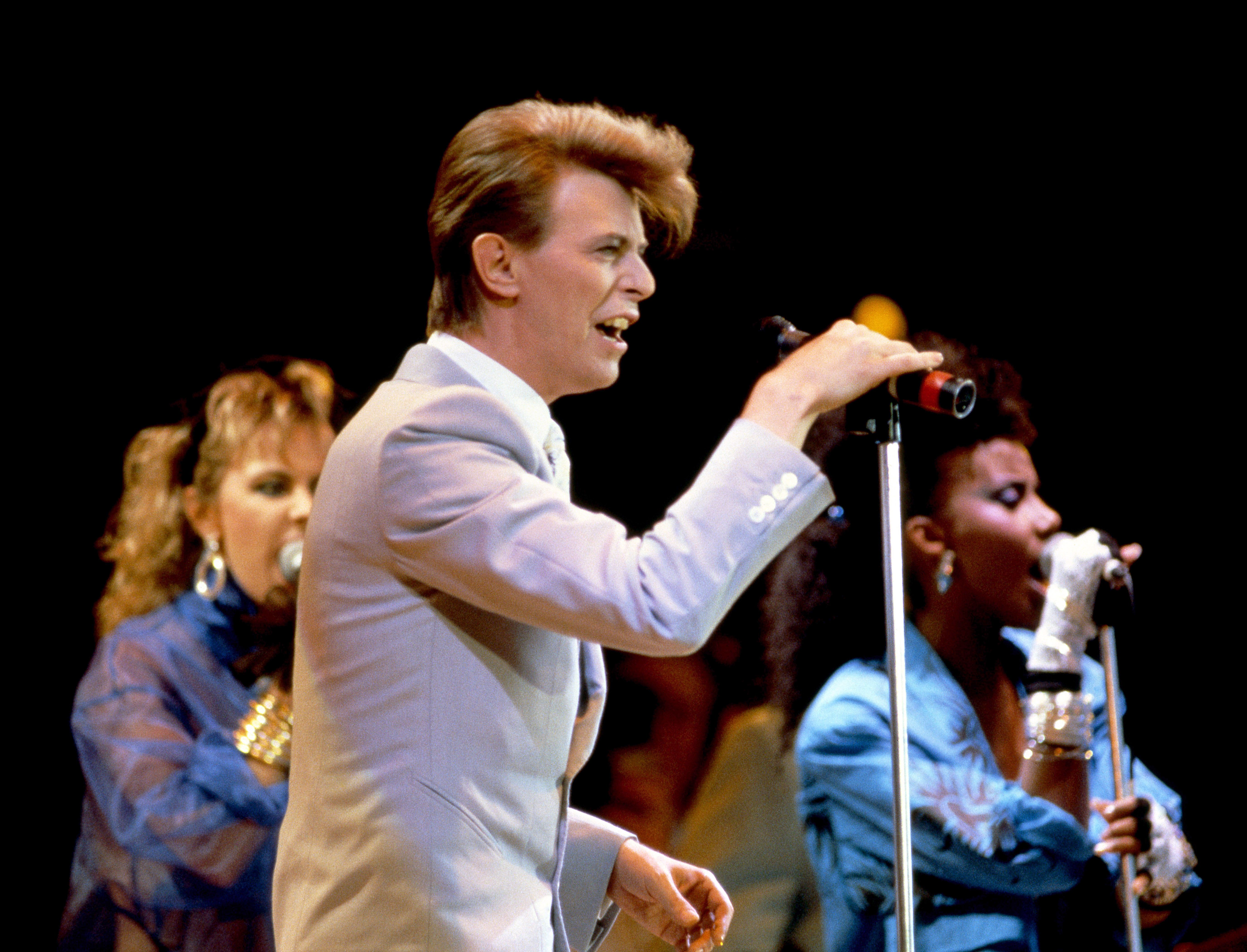 David Bowie with his two backing singers performing at Live Aid. The backing singer on the left is Tessa Niles.