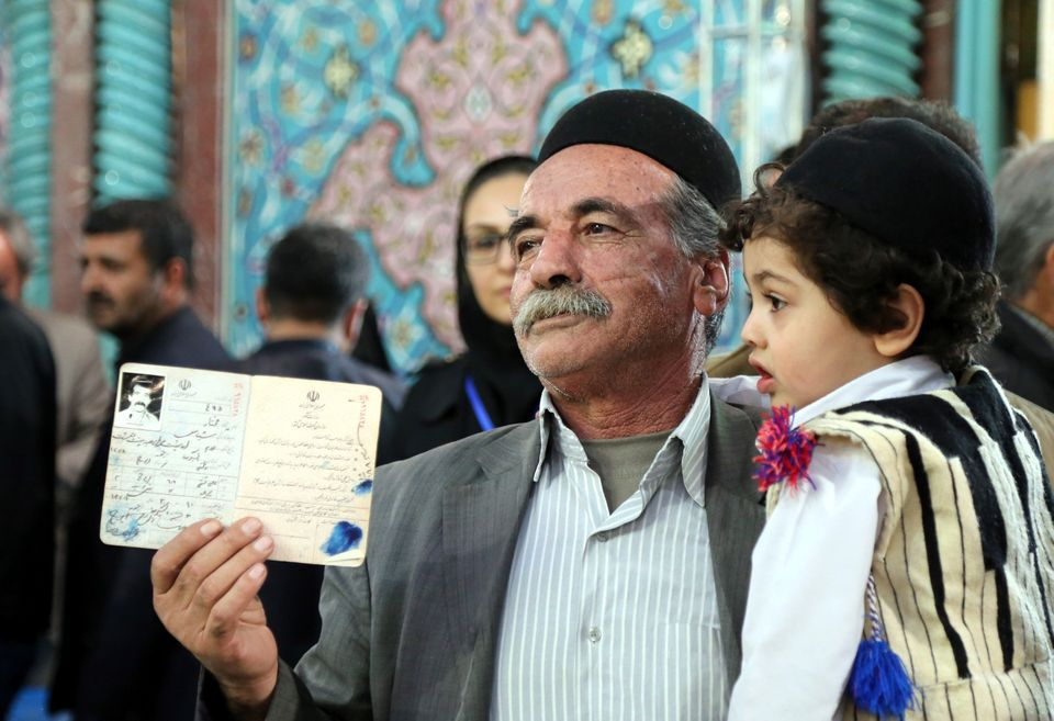 An Iranian man displays his identity document as he waits to cast a ballot for both elections at Husseiniyeh I