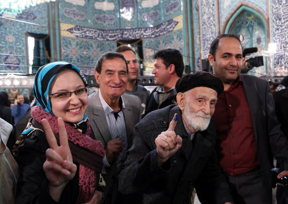 Iranians pose for a photo after voting in both elections in Tehran.