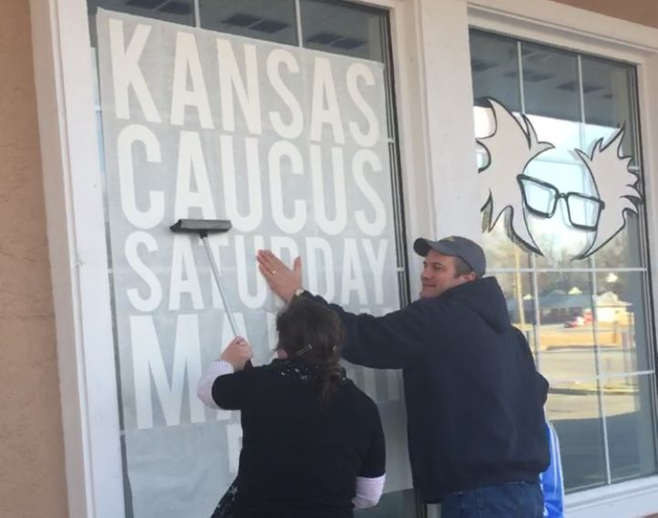 Campaign volunteers put up a sign in the window of Bernie Sanders' Shawnee, Kansas, field office on Feb. 24, 2016.