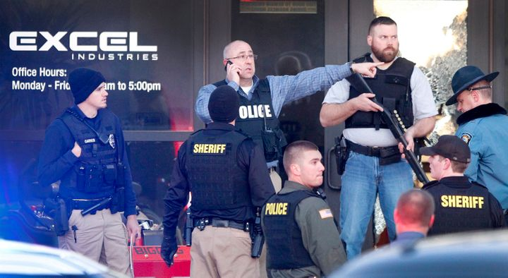 Police guard the front door of Excel Industries in Hesston, Kansas, where a gunman opened fire on Thursday.