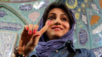 An Iranian woman displays her ink-stained finger after casting her ballot for both parliamentary elections and the Assembly of Experts at a polling station in Tehran on February 26, 2016. Iranians began voting across the country in elections billed by the moderate president as vital to curbing conservative dominance in parliament and speeding up domestic reforms after a nuclear deal with world powers. / AFP / ATTA KENARE        (Photo credit should read ATTA KENARE/AFP/Getty Images)