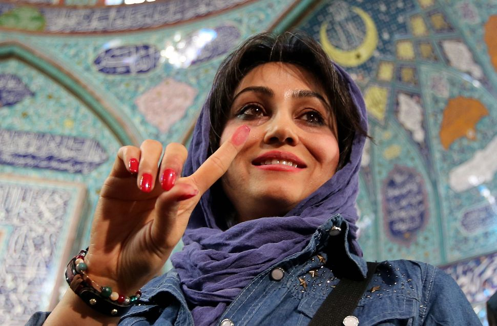 An Iranian woman proudly displays her ink-stained finger after casting her ballot at a polling station in Tehran on Feb.&nbsp