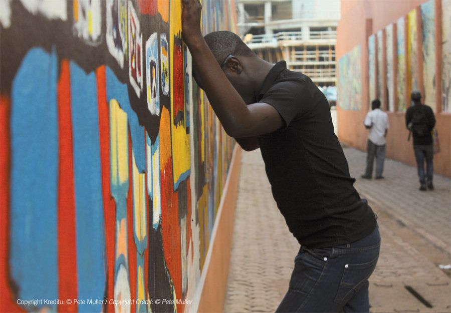 A young man leans against a wall in his neighborhood, where he has been frequently beaten and humiliated, due to his sexual o
