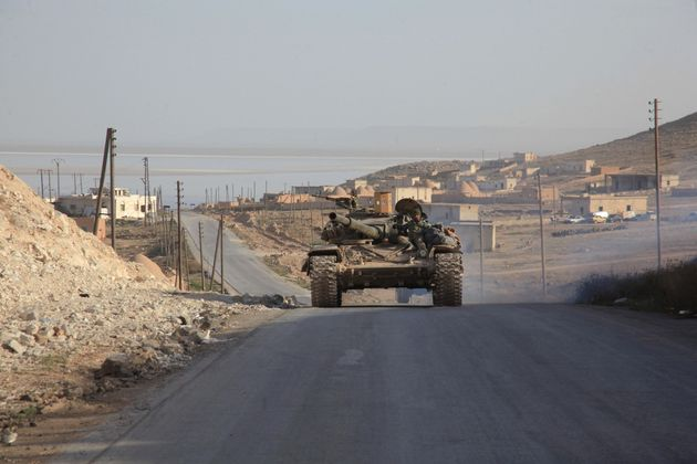 Syrian government forces drive a tank on a road during a military operation in the Aleppo area on
