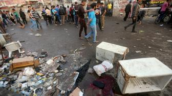 Iraqis inspect the damage at the site of a bombing claimed by the Islamic State (IS) group near a market in the Sadr City area of northern Baghdad, on February 28, 2016.  IS also attacked an army position west of Baghdad, temporarily holding it and killing at least eight security personnel over the course of the day. The two blasts near a market in the Sadr City, at least one of which was a suicide bombing, also wounded at least 64 people, security and medical officials said.  / AFP / AHMAD AL-RUBAYE        (Photo credit should read AHMAD AL-RUBAYE/AFP/Getty Images)