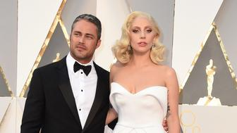 Singer Lady Gaga and Taylor Kinney arrive on the red carpet for the 88th Oscars on February 28, 2016 in Hollywood, California. AFP PHOTO / VALERIE MACON / AFP / VALERIE MACON        (Photo credit should read VALERIE MACON/AFP/Getty Images)