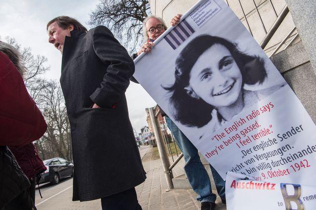 An activist rolls up a poster featuring Holocaust victim Anne Frank outside the Neubrandenburg court...