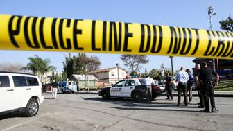 Police officers investigate the scene near Pearson Park in Anaheim, California,  February 27, 2016, after three counter-protesters were stabbed while clashing with Ku Klux Klan members staging a rally. Thirteen people were arrested. / AFP / RINGO CHIU        (Photo credit should read RINGO CHIU/AFP/Getty Images)