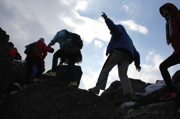 The Ascend hiking team balances on boulders as they make their way up a