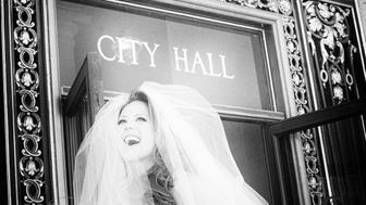 Bride standing in front of city hall with her bouquet in black and white.