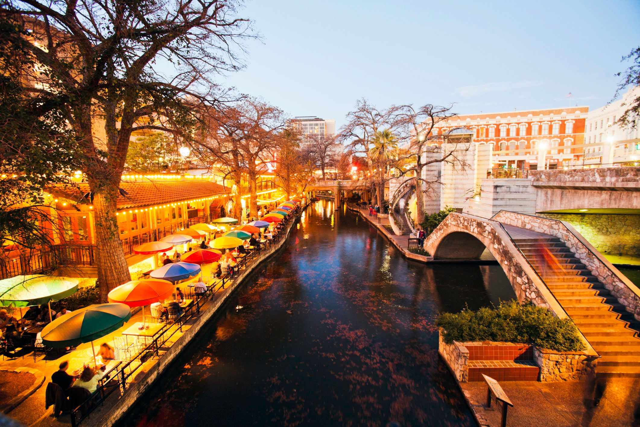 San Antonio River Walk of bridge and rainbow colored umbrellas at dusk, San Antonio, Texas, USA