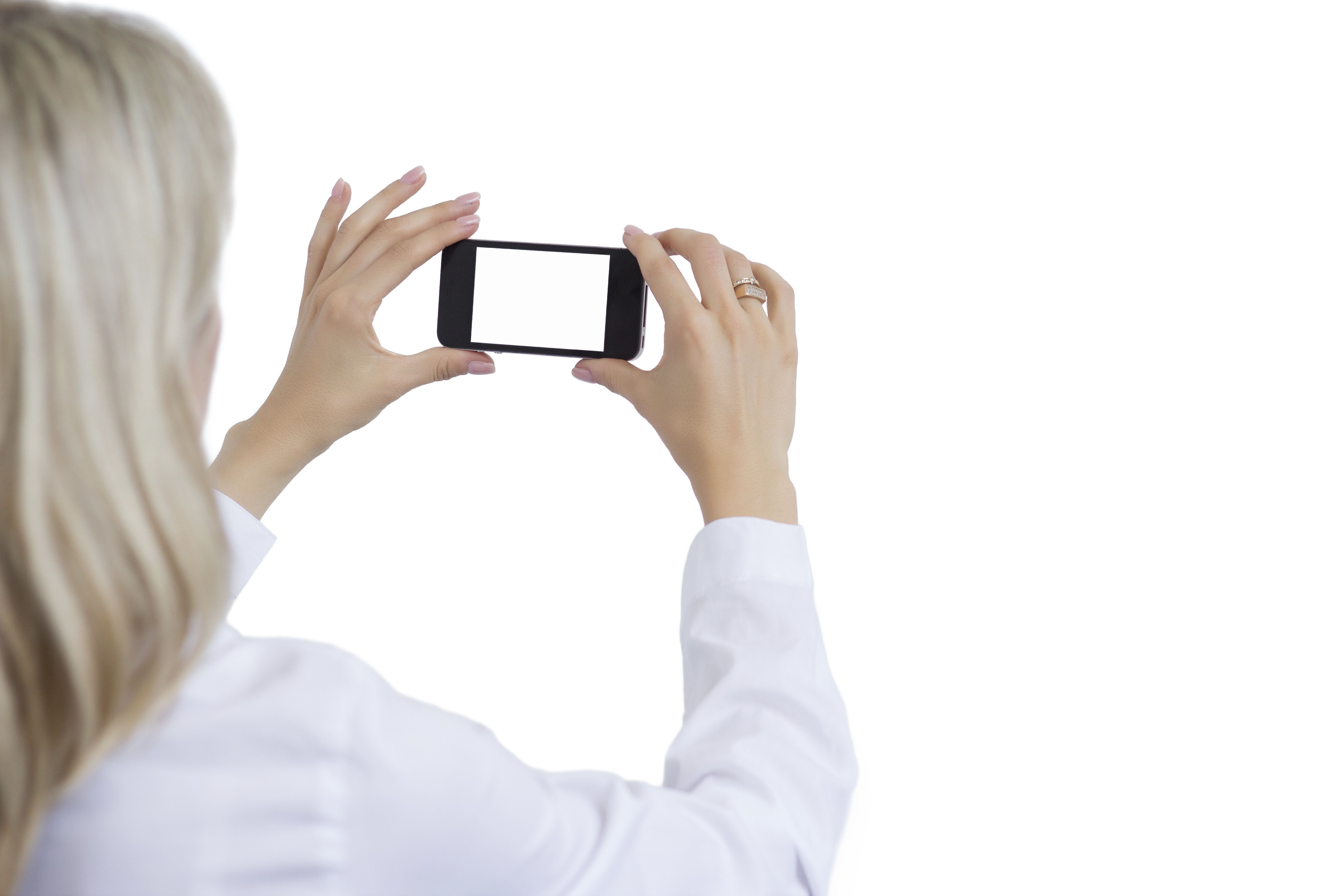 Woman taking photo with mobile phone. Isolated white background and empty phone's screen for your own image.