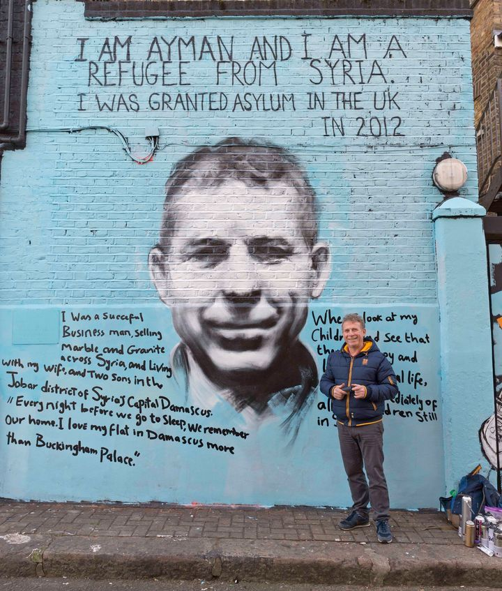 Ayman Hirh stands in front of the striking mural that he created with London street artist PANG.