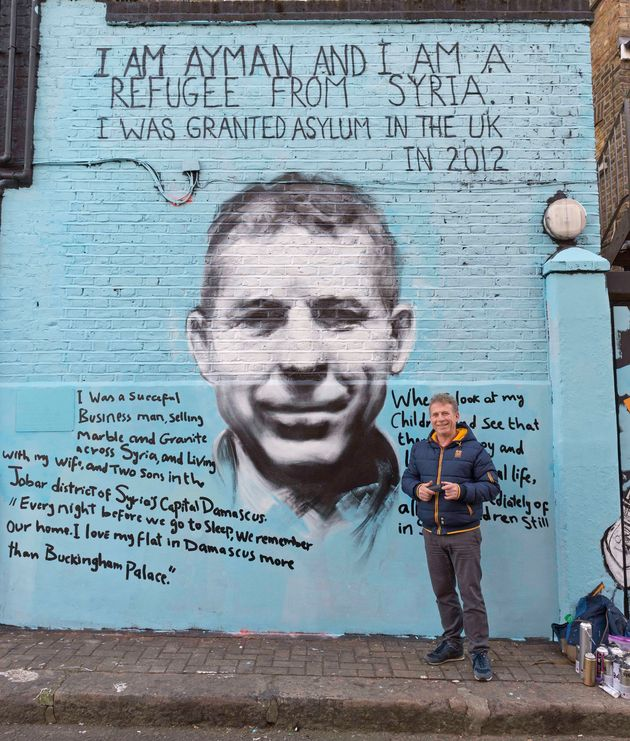 Ayman Hirh stands in front of the striking mural that he created with London street artist