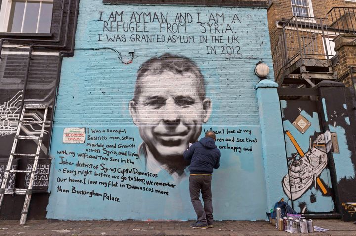 Ayman Hirh hand writes out his poignant messages on PANG's street mural in north London.