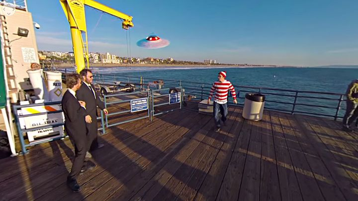 "Two suited sleuths are seen cornering Waldo after tracking him down on the Santa Monica pier in the ""Where's Waldo?"" 360-vide"
