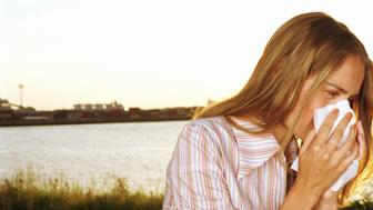 Young woman holding tissue to nose outdoors