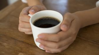 A woman's hands holding the coffee cup.