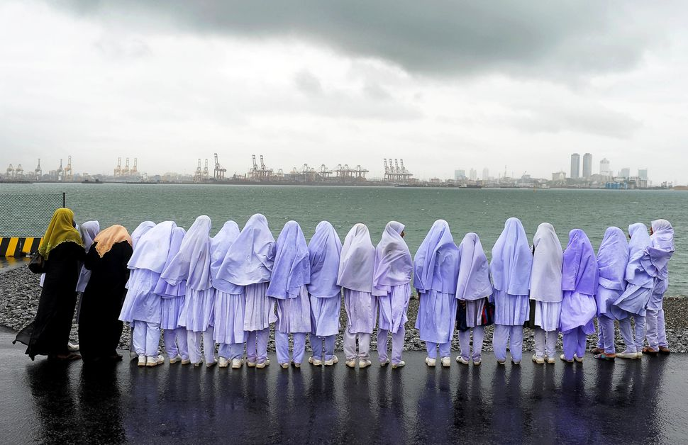 Sri Lankan Muslim school girls stand on the edge of a sea port in Colombo on May 20, 2013, after traveling from their town of
