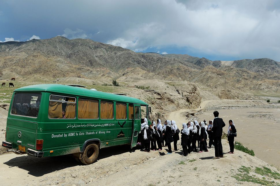 Afghan schoolgirls board a bus in Qara Zaghan village in Baghlan province on May 7, 2013.