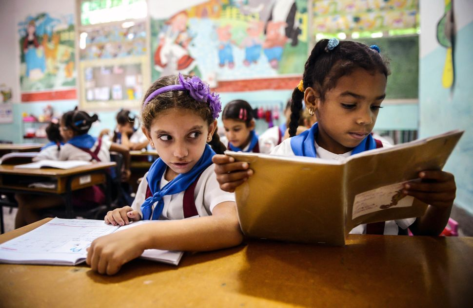 Cuban schoolgirls read during class on November 13, 2012 in Havana.