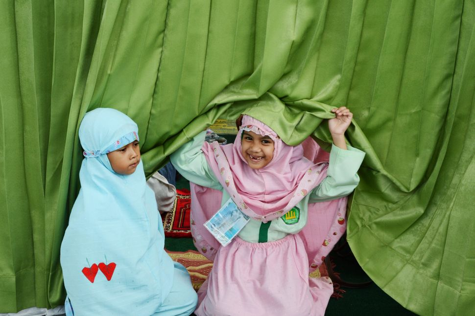 Two Islamic school children prepare for prayer during a school trip in Jakarta on October 18, 2012.