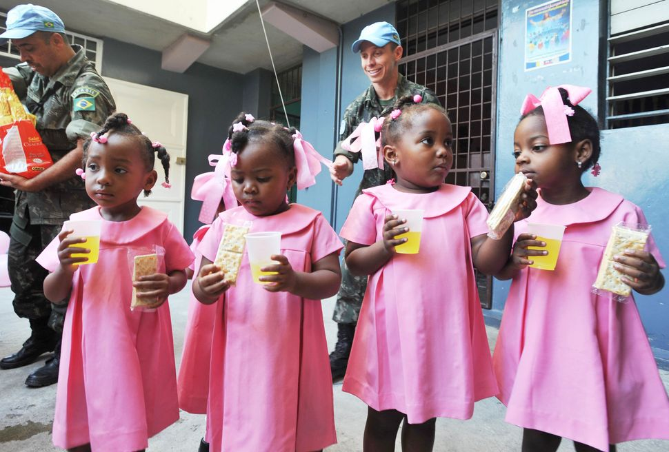 Brazilian UN peacekeepers distribute juice and crackers to students at the Immaculate Conception School February 6, 2013 in P