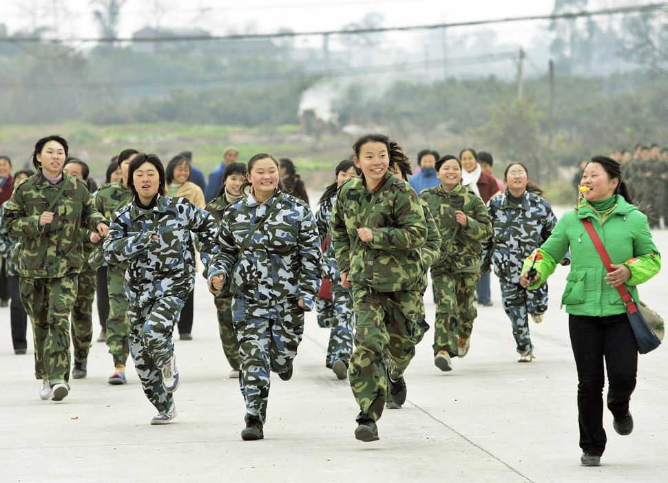 "A class of students run during a physical training exercise at the temporary campus of the ""Walking School"" of Xu Xiangyang E"