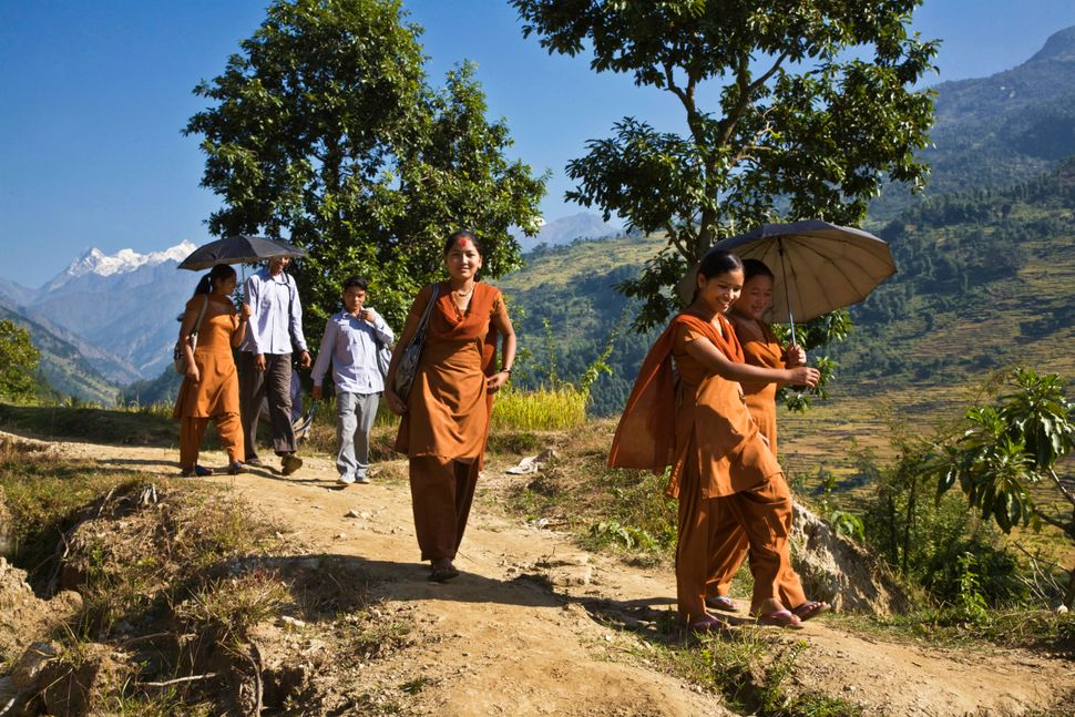 School girls in orange uniforms walk to school along a trail around Manaslu Trek, Nepal.