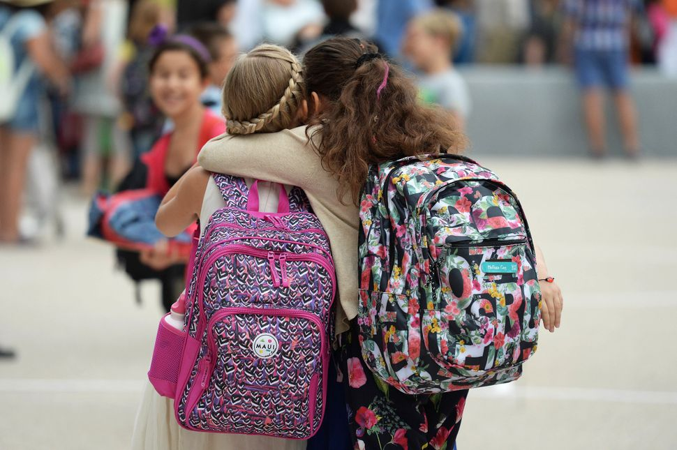 Girls hug each other on the first day of school outside the European School of Strasbourg in Strasbourg, France on September