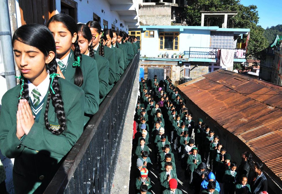 Indian schoolchildren pray during morning assembly at their school in Shimla on December 17, 2014, as they pay tribute to sla