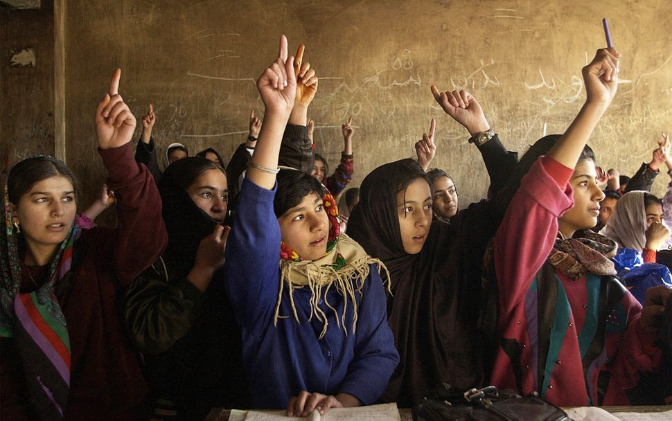 ––Afghani girls raise their hands to answer a question in math class. ––