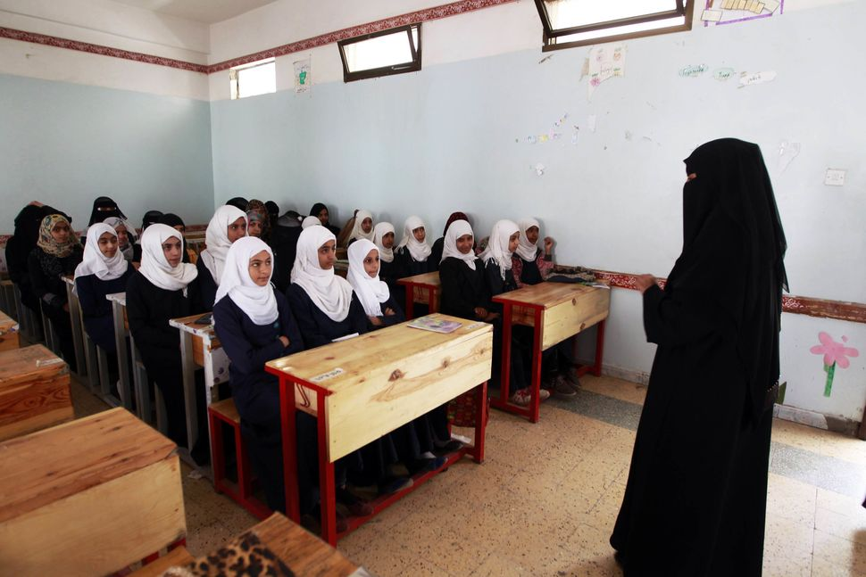 Yemeni girls listen to their teacher on their fist day of school at a public institution in the Yemeni capital Sanaa on Novem