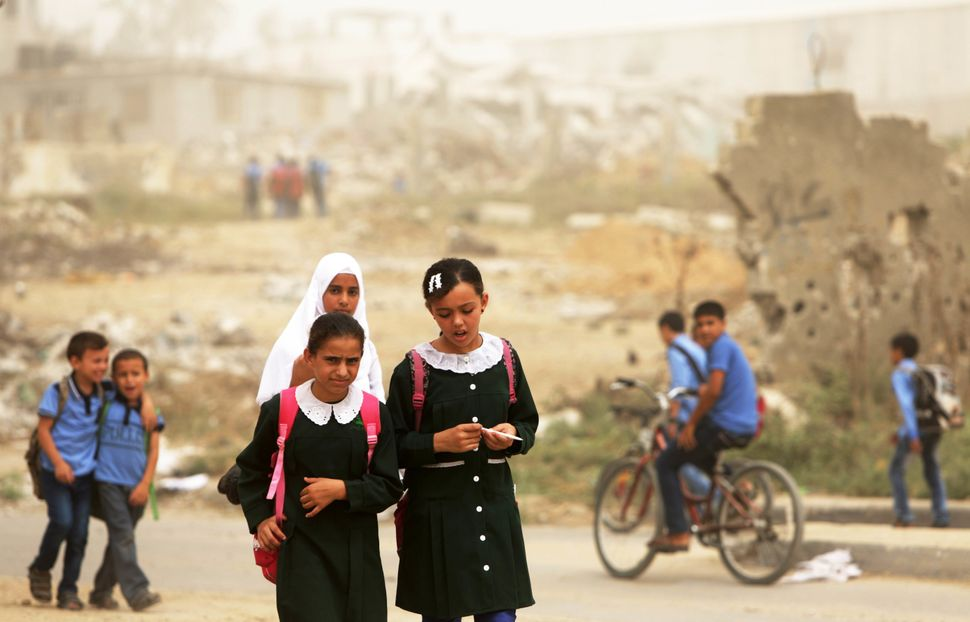Palestinian school girls walk during a sandstorm in Gaza City on September 9, 2015.