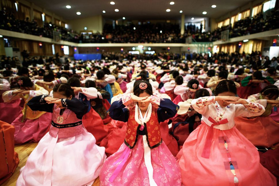 Students wearing traditional hanbok dresses bow as they attend a graduation and coming-of-age ceremony at the Dongmyeong girl