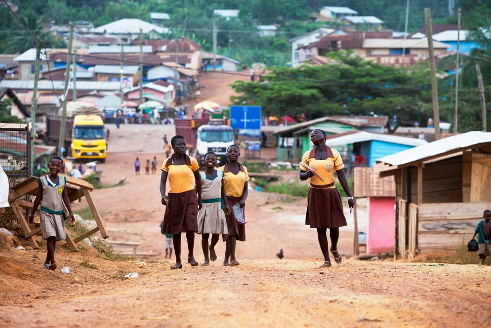 School girls head home through their cocoa-producing village on November 11, 2015 in Akyekyere, Ghana.
