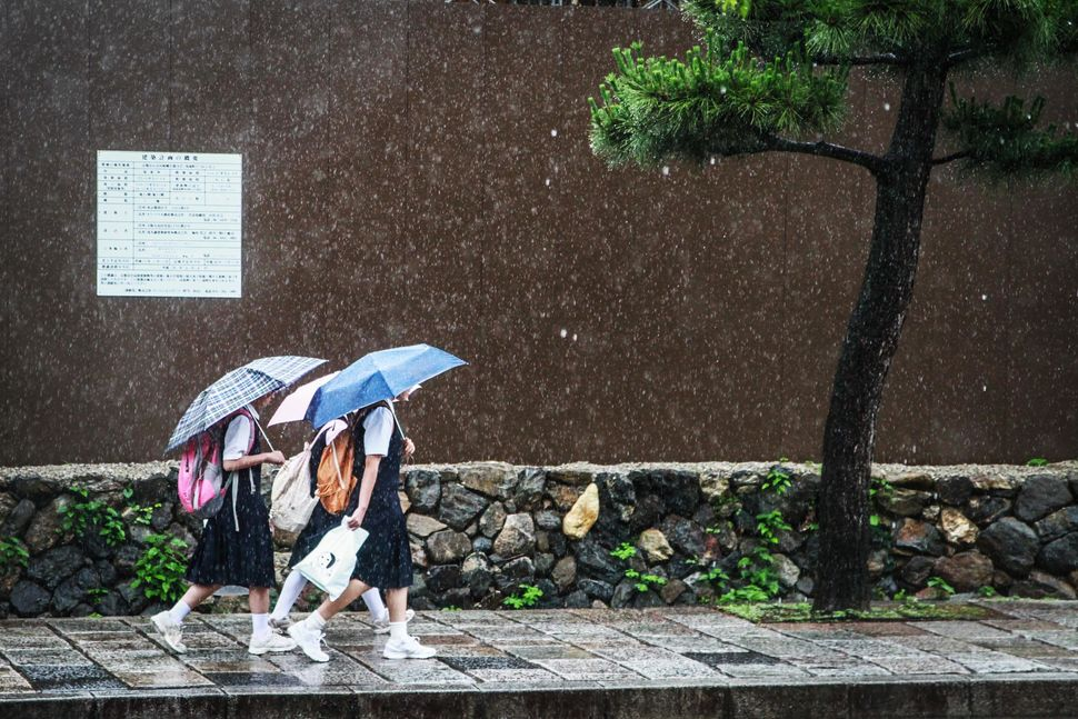 Student walk to school the rain in June 2013 in Kyoto, Japan.