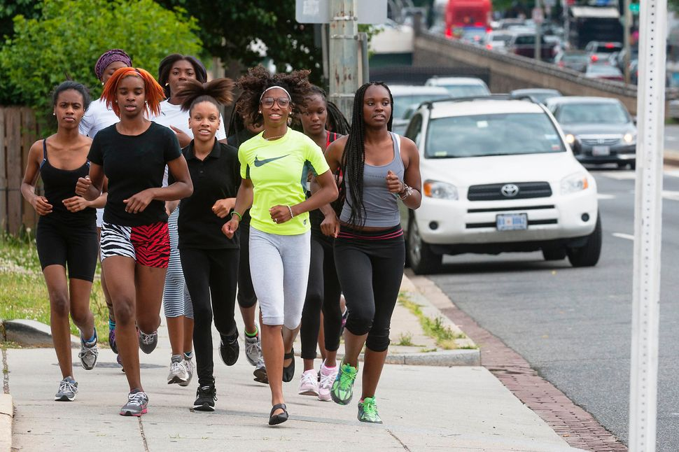 A girls' track team runs through traffic as they travel to McKinley High School where they practice on May 28, 2013 in Washin