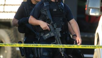 LOS ANGELES, CALIFORNIA., AUGUST 18, 2014: Los Angeles Police Department SWAT officers walk towards their vehicles after one officer was wounded and a suspect killed at the end of a pursuit and gun battle near the intersection of 37th Street and South Grand Avenue South Los Angeles, August 18, 2014. A second suspect was arrested after he was found hiding in a dumpster a few blocks away (^^^ / Los Angeles Times ).  (Photo by Mark Boster/Los Angeles Times via Getty Images)