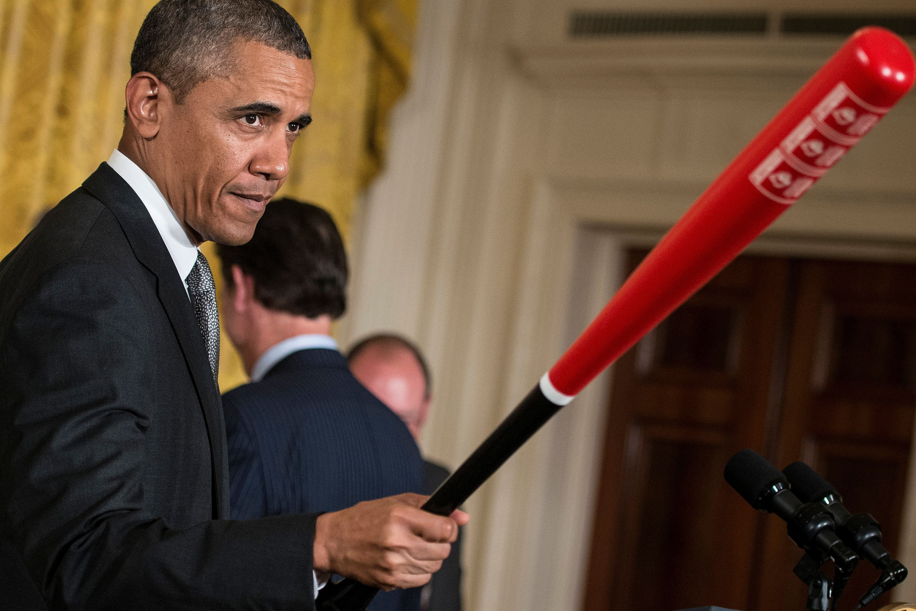 US President Barack Obama holds a Louisville Slugger baseball bat given to him by Louisville coach Rick Pitino during an event in the East Room of the White House July 23, 2013 in Washington, DC. Obama attended the event with the Louisville Cardinals to honor their 2013 NCAA Mens Basketball Champion win. AFP PHOTO/Brendan SMIALOWSKI        (Photo credit should read BRENDAN SMIALOWSKI/AFP/Getty Images)