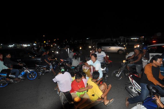 Indonesian residents use a variety of transport options as they rush to higher ground in Padang late...