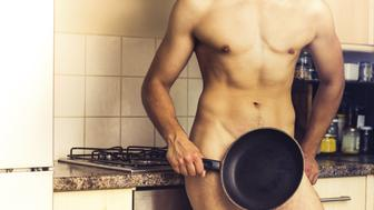 Naked young man with toned muscles is standing in front of the cooker in a domestic kitchen covering his private parts with a frying pan