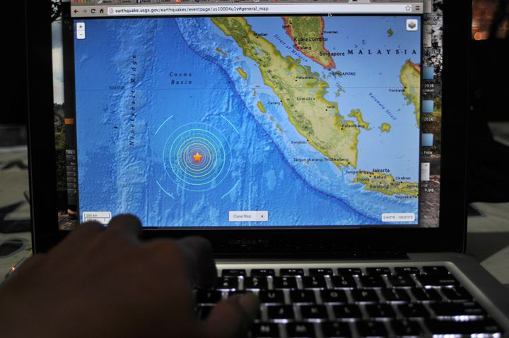 An Indonesia man read news of the earthquake that shook the Mentawai islands on the internet that just happened, in Jakarta,