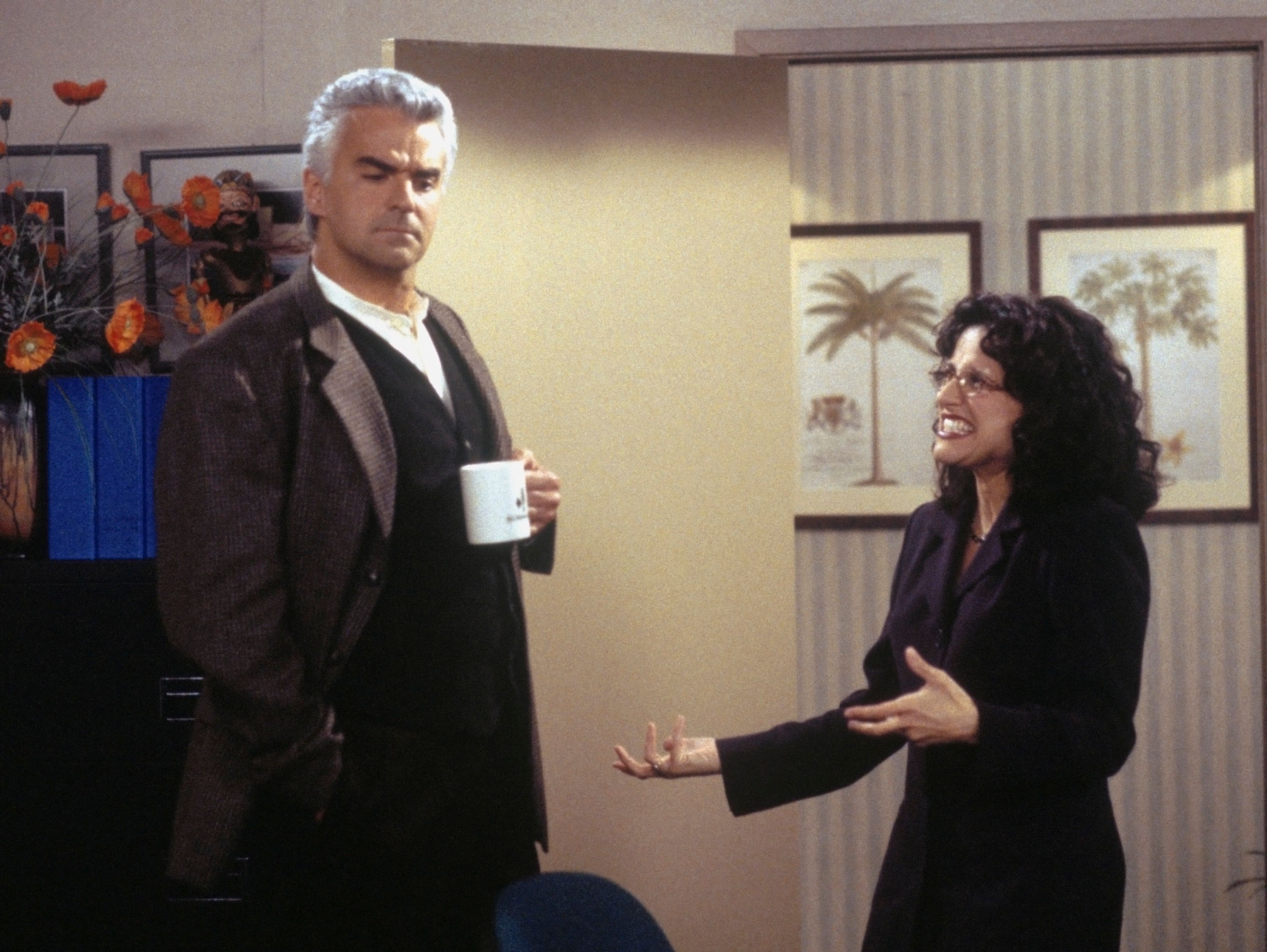 """SEINFELD -- """"The Bookstore"""" Episode 17 -- Pictured: (l-r) John O'Hurley as J. Peterman, Julia Louis-Dreyfus as Elaine Benes  (Photo by Joey Delvalle/NBC/NBCU Photo Bank via Getty Images)"""