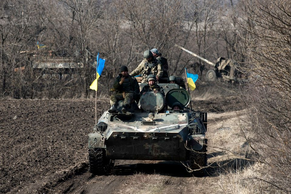 Ukrainian servicemen ride atop armored vehicle with a cannon in tow and Ukrainian flags, near the village of Fedorivka, easte